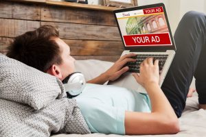 Man lying at home using a laptop to book travel destination.